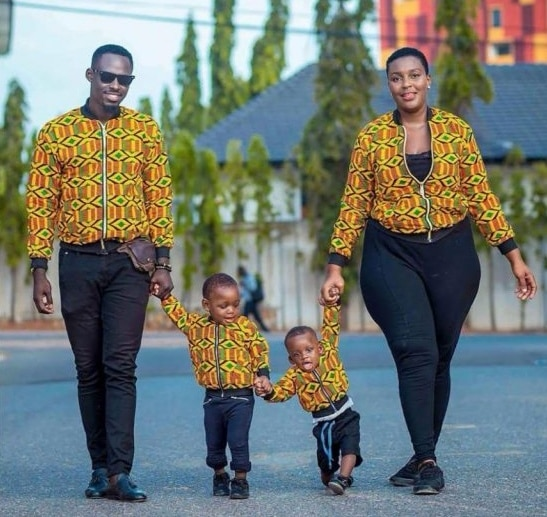 Shot of couple with children wearing matching kids bomber jacket in African Kente print.