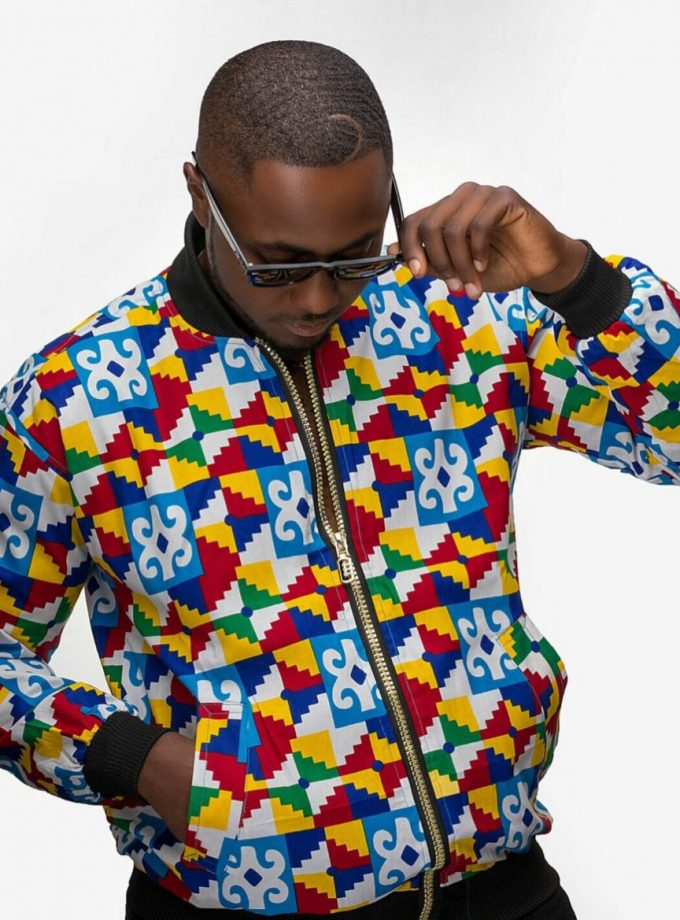 Frontal of model wearing an African inspired unisex bomber jacket in all over vibrant multi-coloured African Kente print.